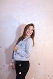 Mujer bonita con la sonrisa que presenta en la cámara, colocándose en fondo Fotos de archivo