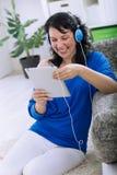 Mujer bonita con la tableta y los auriculares en casa Imagenes de archivo