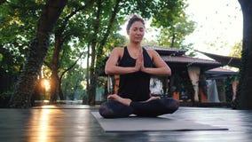 Mujer bonita con la yoga practicante de la cara oriental, mudra de la gratitud del namaste solamente en la isla tropical Muchacha metrajes