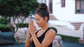 Mujer bonita con la yoga practicante de la cara oriental, mudra de la gratitud del namaste solamente en la isla tropical Religión metrajes