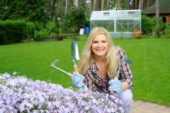 Mujer bonita con las herramientas que cultivan un huerto al aire libre Imagen de archivo libre de regalías
