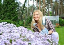 Mujer bonita con las herramientas que cultivan un huerto al aire libre Foto de archivo libre de regalías