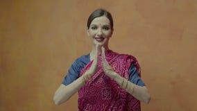 Mujer bonita con las manos unidas en el saludo del namaste almacen de metraje de vídeo