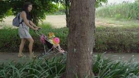 Mujer bonita con las trenzas africanas que llevan a la niña en cochecito de niño almacen de video