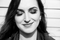 Mujer bonita con los ojos cerrados, el pelo largo, los labios sensuales y el maquillaje profesional colocándose en la calle Rebec Imagenes de archivo