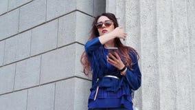 Mujer bonita con un smartphone en la calle almacen de video