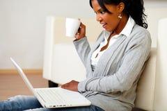Mujer bonita con una taza que hojea el Internet Fotografía de archivo libre de regalías