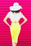 Mujer bonita de la moda de la silueta en falda del sombrero de paja del verano sobre rosa colorido Foto de archivo