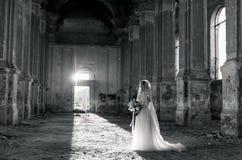 Mujer bonita de la novia en vestido blanco elegante del cordón con el ramo de la boda Foto de archivo
