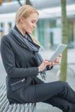 Mujer bonita de la oficina que usa su artilugio al aire libre Foto de archivo