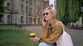 Mujer bonita de moda en las gafas de sol que sostienen el café y que hablan en el teléfono, sentándose en parque cerca de univers almacen de metraje de vídeo