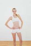 Mujer bonita del ajuste que presenta en ropa de deportes con las manos en caderas Fotos de archivo libres de regalías