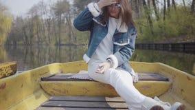 Mujer bonita del encanto en los pantalones blancos y las gafas de sol que se sientan en el barco amarillo viejo en el río, mirand almacen de metraje de vídeo