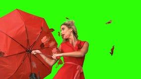 Mujer bonita del encanto que sostiene un paraguas quebrado en la pantalla verde almacen de video