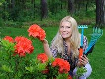 Mujer bonita del jardinero con las herramientas que cultivan un huerto Foto de archivo