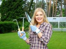 Mujer bonita del jardinero con las herramientas que cultivan un huerto Foto de archivo libre de regalías