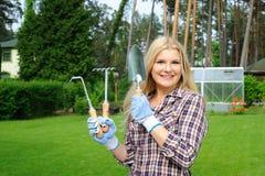 Mujer bonita del jardinero con las herramientas que cultivan un huerto Imagenes de archivo