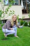 Mujer bonita del jardinero con las herramientas que cultivan un huerto Imagen de archivo libre de regalías