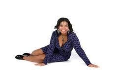 Mujer bonita del negro que se sienta en alto fondo dominante Imagenes de archivo
