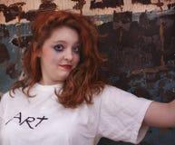Mujer bonita del pelirrojo contra la pared de la construcción Imagen de archivo libre de regalías
