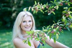 Mujer bonita del resorte en un jardín verde cerca del árbol Imagenes de archivo
