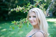 Mujer bonita del resorte en un jardín verde cerca del árbol Imagen de archivo
