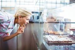 Mujer bonita desconcertada que mira las tortas de la taza Fotografía de archivo