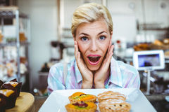 Mujer bonita desconcertada que mira una empanada de la fruta Imagenes de archivo