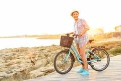 Mujer bonita despreocupada con el montar a caballo de la bicicleta en una trayectoria de madera en el th Imagen de archivo libre de regalías
