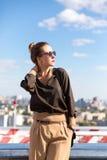 Mujer bonita elegante del retrato de la moda de la calle con las gafas de sol y bolso que presenta en ciudad en la igualación de  Foto de archivo