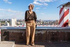 Mujer bonita elegante del retrato de la moda de la calle con las gafas de sol y bolso que presenta en ciudad en la igualación de  Fotos de archivo