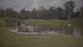 Mujer bonita elegante que descansa en parque del verano almacen de video