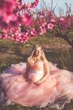 Mujer bonita embarazada en jardín del flor de la primavera Imagenes de archivo