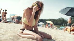 Mujer bonita en bikini que habla en el teléfono en la playa almacen de metraje de vídeo