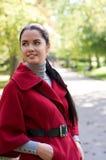 Mujer bonita en capa roja en el parque del otoño. Foto de archivo libre de regalías