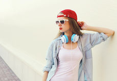 Mujer bonita en casquillo y gafas de sol rojos con los auriculares sobre blanco Fotografía de archivo libre de regalías