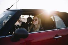 Mujer bonita en coche convertible de la moda en puesta del sol Fotografía de archivo libre de regalías