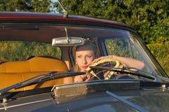 Mujer bonita en coche viejo en la puesta del sol Foto de archivo