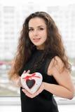 Mujer bonita en el amor que sostiene el rectángulo en forma de corazón Imagen de archivo