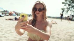 Mujer bonita en el bikini que se sienta en la playa y que toma un selfie almacen de metraje de vídeo