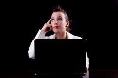 Mujer bonita en el ordenador, mirada de pensamiento para arriba Foto de archivo libre de regalías