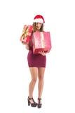 Mujer bonita en el sombrero de santa que abre un regalo que sonríe en él Fotos de archivo