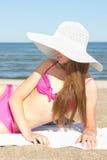 Mujer bonita en el traje de baño rosado que miente en la playa Foto de archivo libre de regalías
