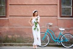 Mujer bonita en el vestido blanco que presenta con las flores y la bici azul delante de la pared roja vieja foto de archivo libre de regalías
