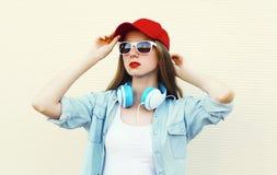Mujer bonita en gafas de sol y casquillo rojo sobre blanco Imagen de archivo
