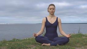 Mujer bonita en la actitud clásica de la yoga, concentración de la energía almacen de metraje de vídeo