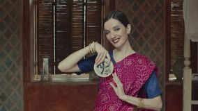 Mujer bonita en la sari que sostiene el instrumento meditativo