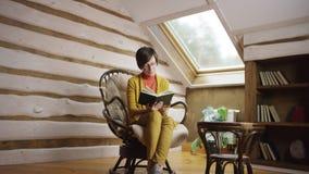 Mujer bonita en libro de lectura de los vidrios en ático almacen de metraje de vídeo