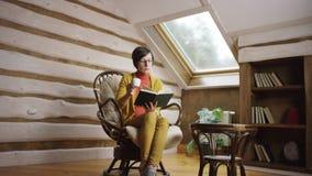 Mujer bonita en libro de lectura de los vidrios mientras que bebe el café en ático almacen de video