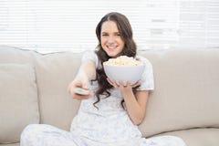 Mujer bonita en los pijamas que comen palomitas mientras que ve la TV Imagenes de archivo